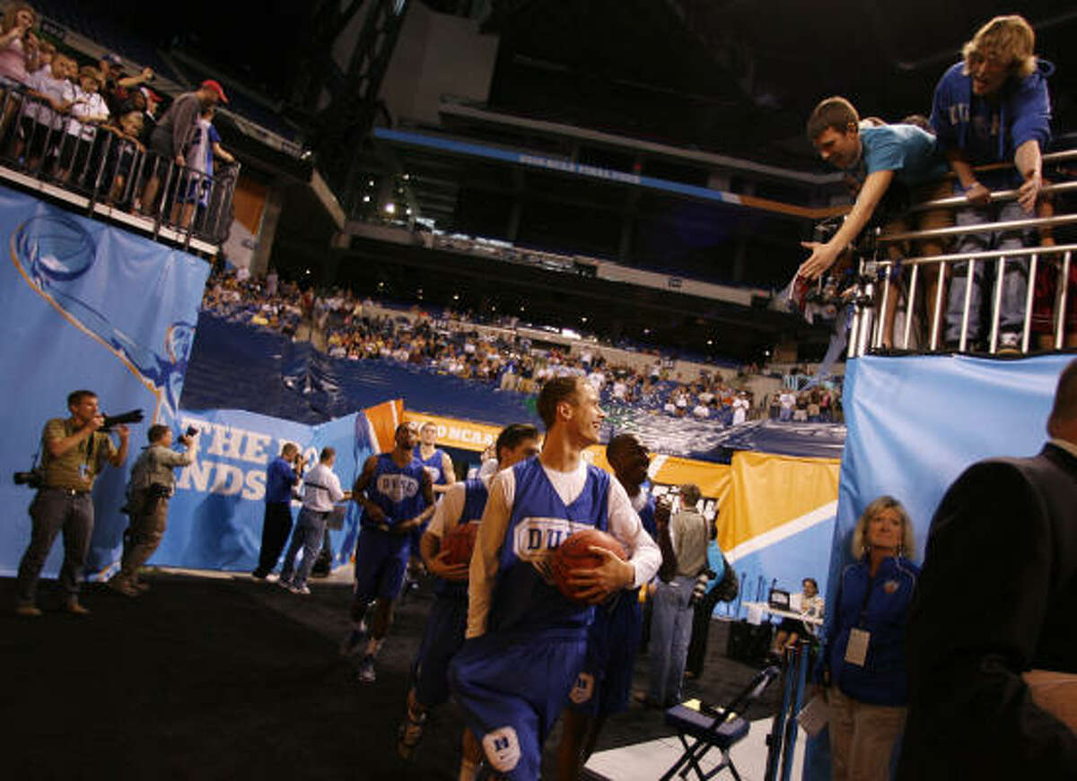 Duke guard Jon Scheyer smiles at the fans as he and his teammates walk out to the court for practice.