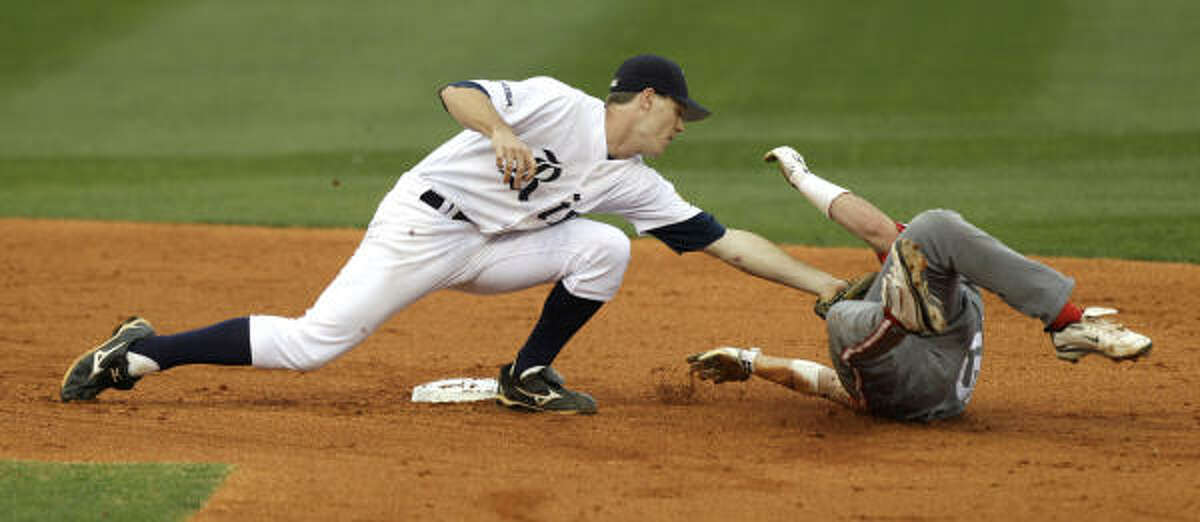 Rice shortstop Jimmy Comerota, left, tags Houston's Zak Presley out at second on a steal attempt.