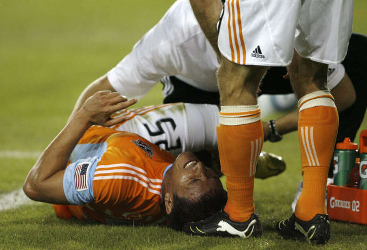 Dynamo forward Brian Ching curls up in pain after being tripped up on a play. Ching strained his left hamstring and had to leave the field of play with the help of trainers during the first half.