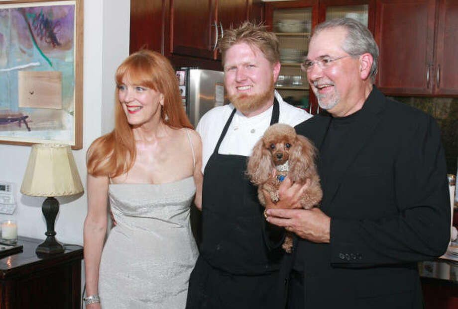 Chef Randy Evans, center, with hosts Gracie and Bob Cavnar at Full Moon Rising, a kickoff party for the annual We're Cooking Now! Gala in Small Bites benefiting the Recipe for Success Foundation. Bob is holding their toy poodle, Mimi. Photo: Gary Fountain, For The Chronicle