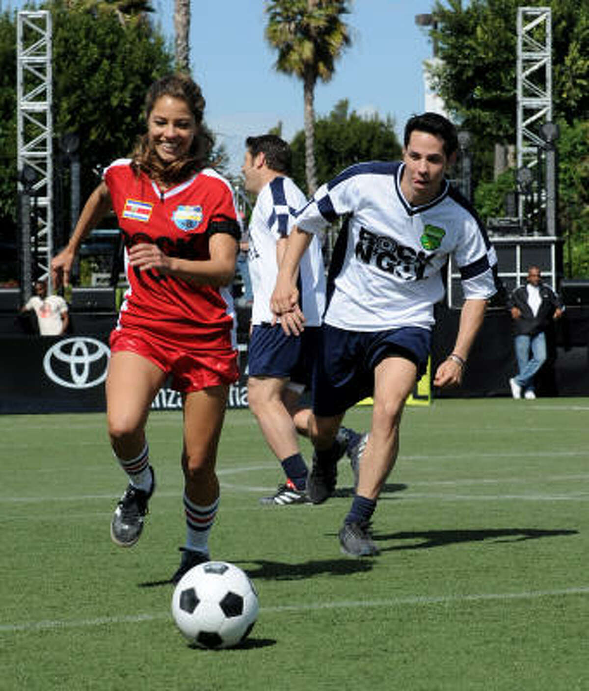 Singer Debi Nova, left, and singer Christian Chavez chase the ball during one of the celebrity matches.