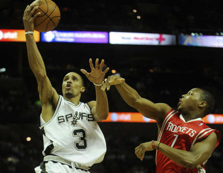Spurs George Hill shoots a layup as Rockets guard Kyle Lowry defends. Photo: BILLY CALZADA, SAN ANTONIO EXPRESS-NEWS