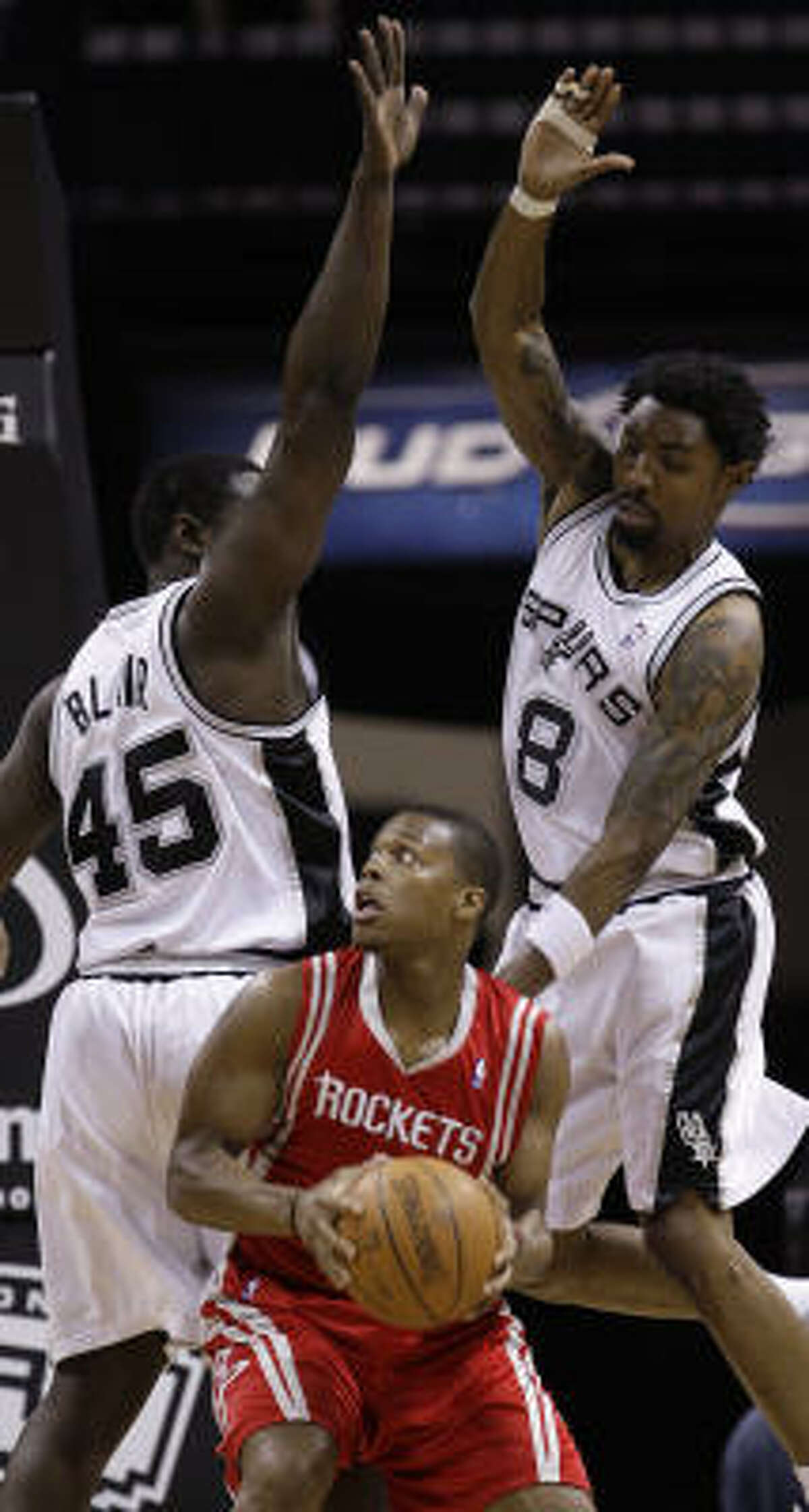 Rockets guard Kyle Lowry, center, is defended by San Antonio Spurs' DeJuan Blair, left, and Roger Mason, Jr.