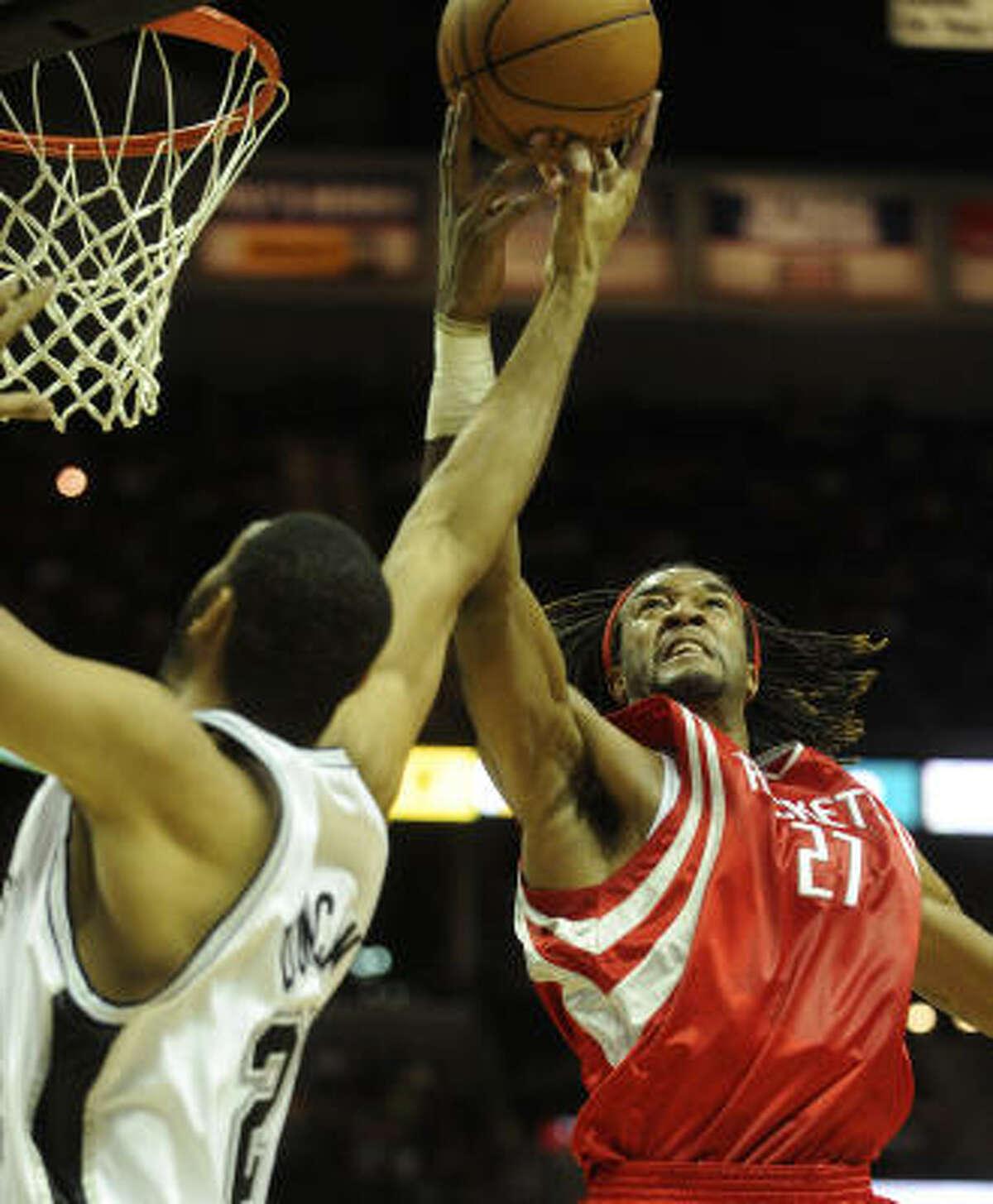 Rockets forward Jordan Hill, right, blocks Spurs' Tim Duncan.