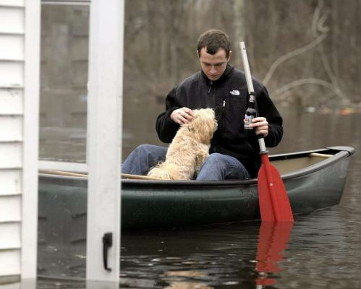 Levi Hill of Groton, Conn., a diver in the U.S. Navy, navigates his canoe to the back door ofhis friend's flooded home, in Westerly, R.I.,