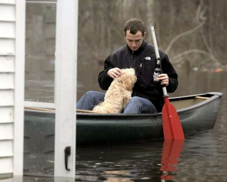 Levi Hill of Groton, Conn., a diver in the U.S. Navy, navigates his canoe to the back door ofhis friend's flooded home, in Westerly, R.I., Photo: TIM MARTIN, The Day
