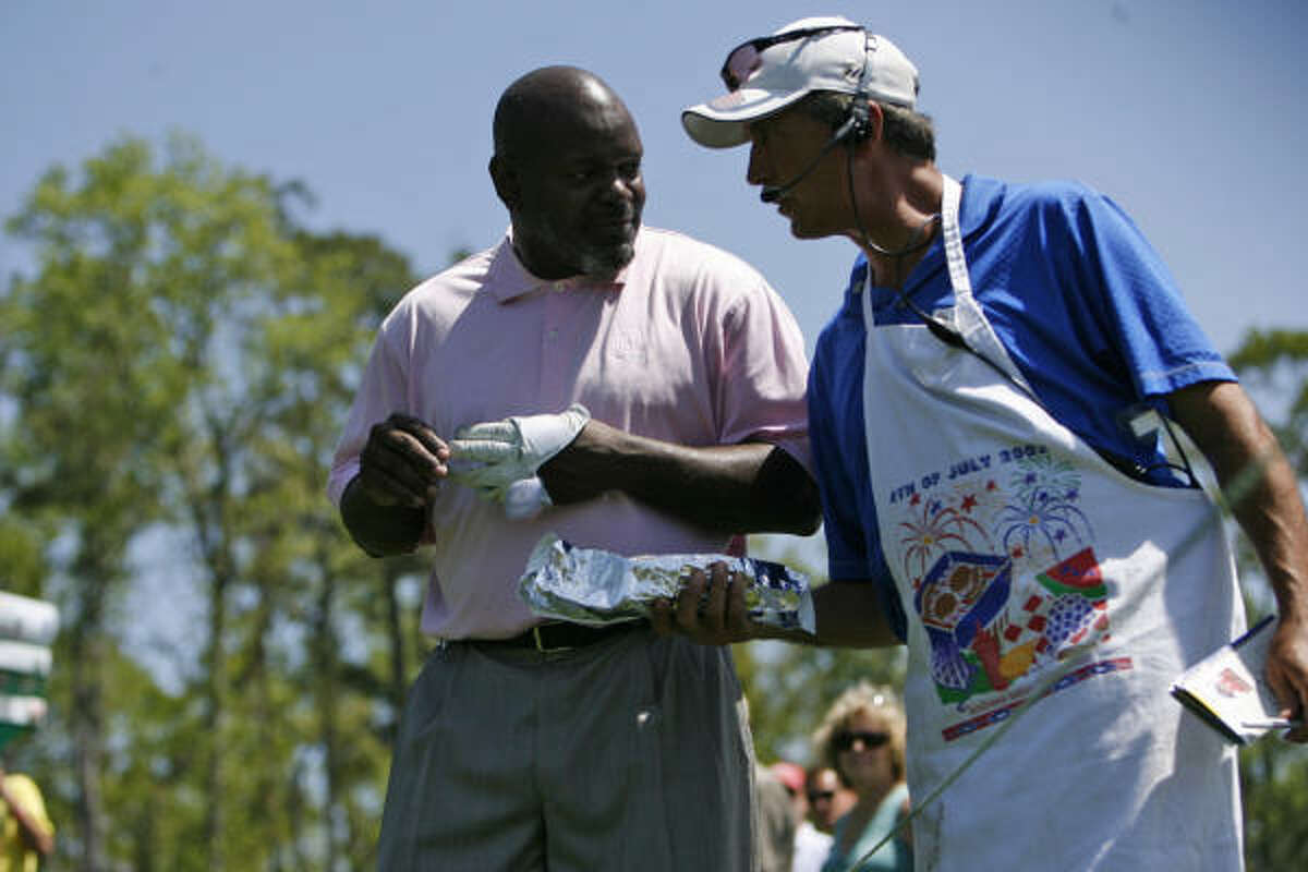 Former Dallas Cowboy, Emitt Smith, left is offered a hot dog during the Shell Houston Open Grand Pro-Am.
