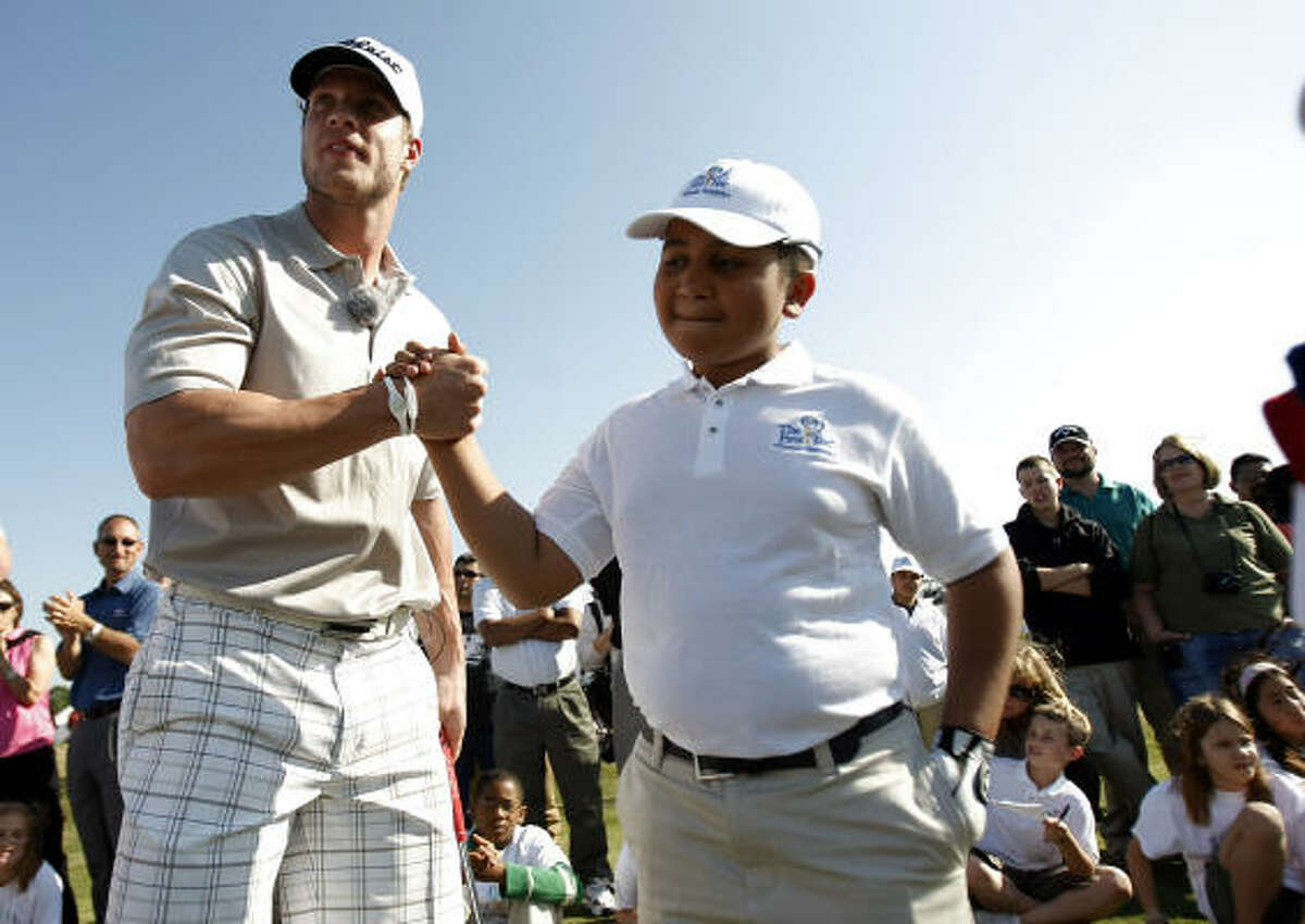 Jonathan Celaya, 11, a Horn Elementary School student and a participant in The First Tee program gets a high five from teammate, Texans wide receiver Kevin Walter during a golf skills event.