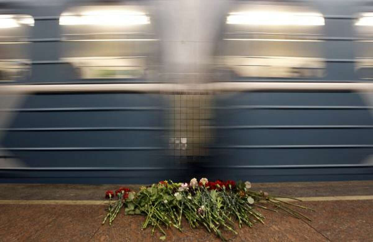 A train passes by the flowers laying at the Lubyanka Subway station's platform. Two female suicide bombers blew themselves up on packed metro trains in Moscow, killing at least 38 people near the ex-KGB headquarters and Gorky Park.