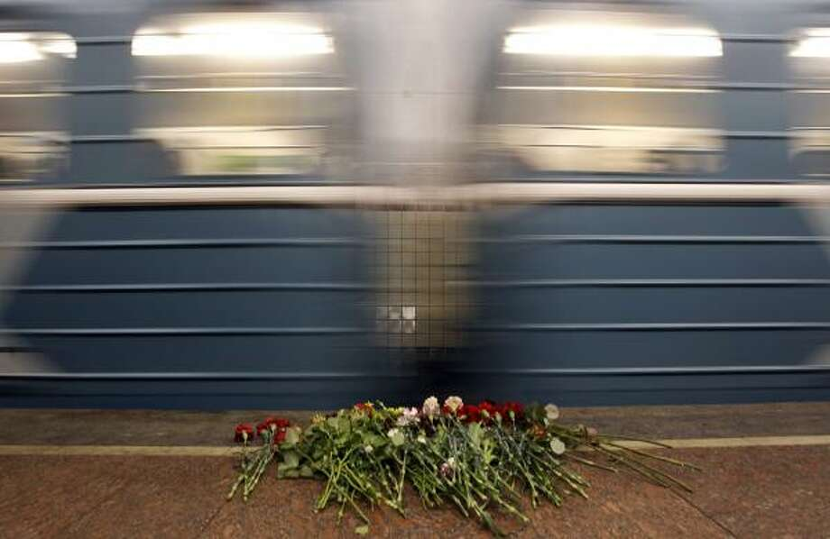 A train passes by the flowers laying at the Lubyanka Subway station's platform. Two female suicide bombers blew themselves up on packed metro trains in Moscow, killing at least 38 people near the ex-KGB headquarters and Gorky Park. Photo: Sergey Ponomarev, AP