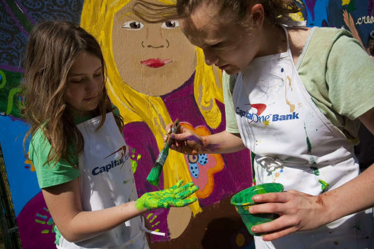 Elena Portz, 16, paints the hand of her sister Anjelika, 11, to contribute to a mural at the 13th Annual Bayou City Art Festival Memorial Park, in Houston. The theme of the mural was environment, arts, music and education, although the children embellished and modified their artwork according to an event volunteer. The festival was a three day, one-of-a-kind outdoor gallery that features fine juried art by 300 top galleried artists from across the country. The festival also had an interactive community mural project open to all festival patrons, an array of multicultural performances on the Houston Arts Alliance stage, and wine and cuisines from all around the world.