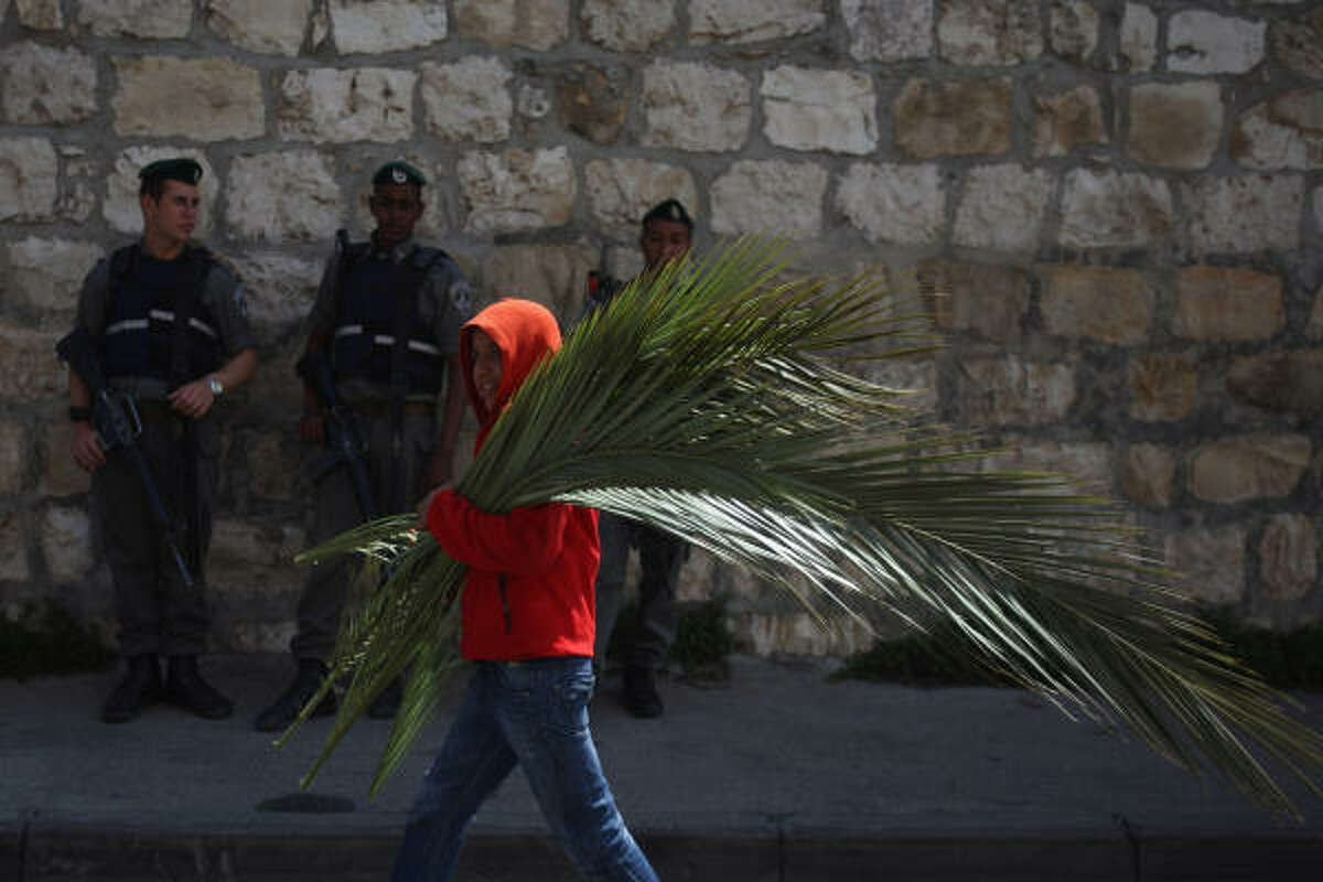 A Palestinian boy carries palm branches for sale to Christian pilgrims past Israeli police guarding the traditional Palm Sunday procession from the Mount of Olives to the Old City in Jerusalem, Israel.
