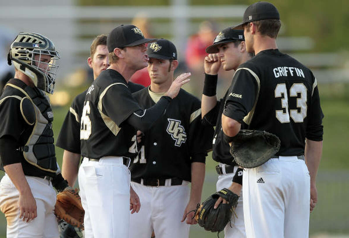 Central Florida coach Terry Rooney has words with his pitcher and infield.