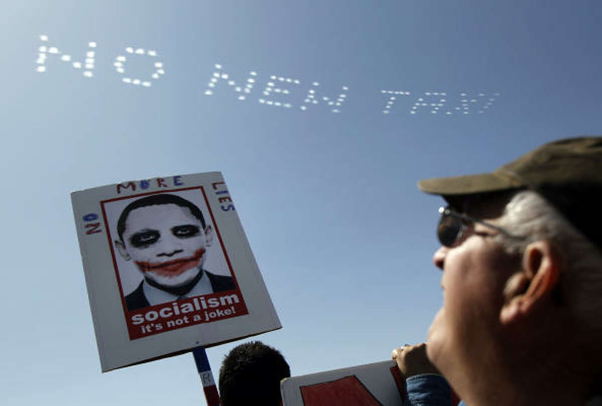 A demonstrator stares at a message in the sky at the