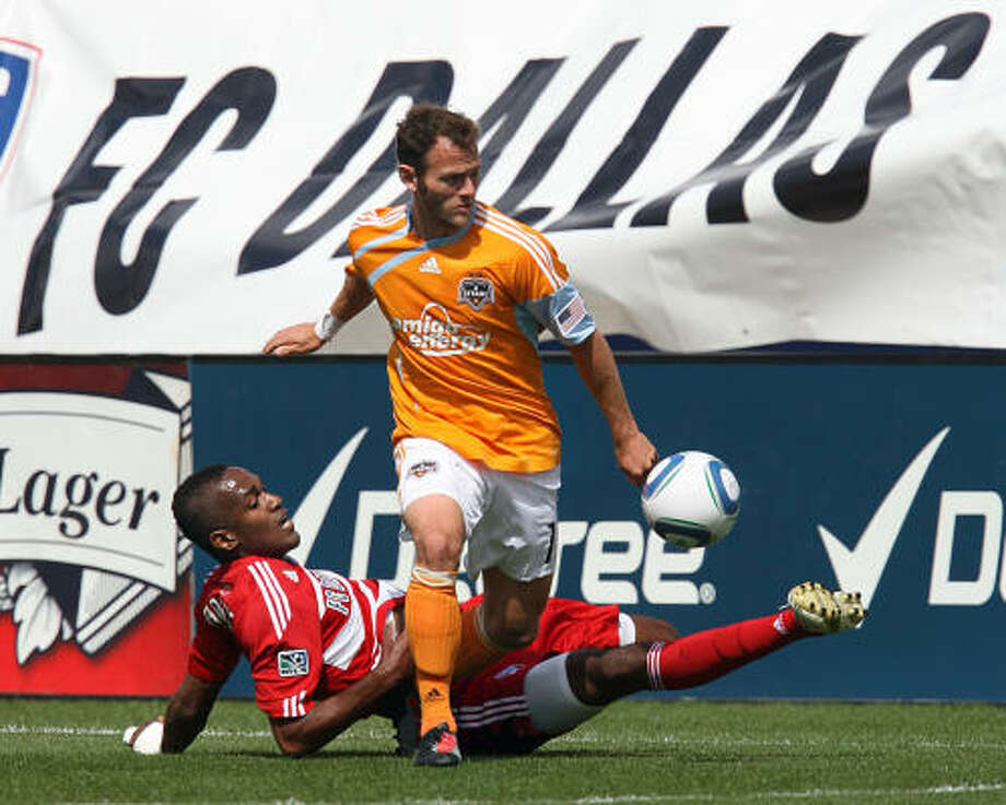 Dynamo midfielder Brad Davis, top, and FC Dallas forward Atiba Harris battle for control of the ball in Saturday's season opener in Frisco. The game ended in a 1-1 tie. Photo: Tom Pennington, Getty Images