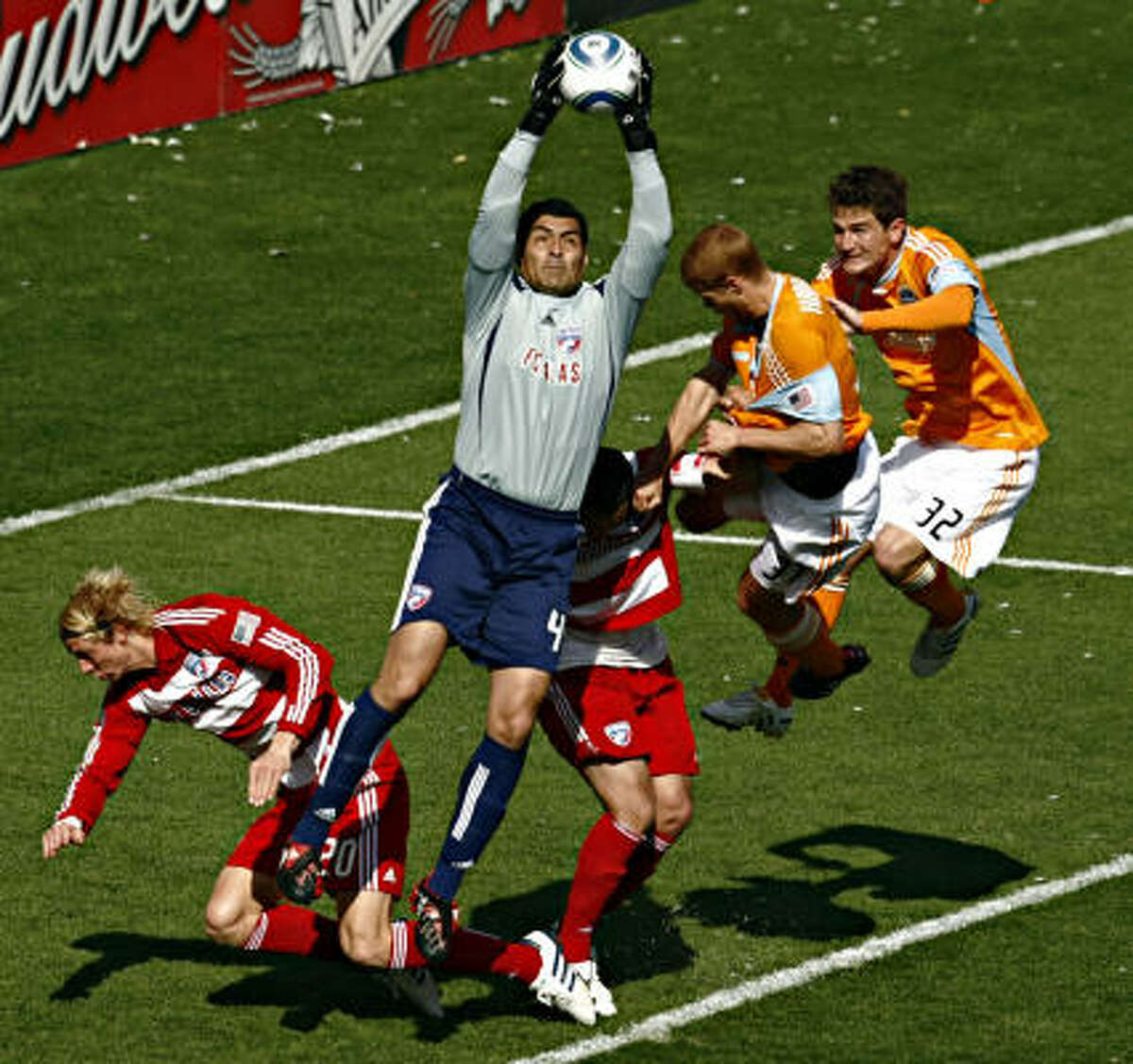FC Dallas goalkeeper Kevin Hartman reaches high to snag the ball.