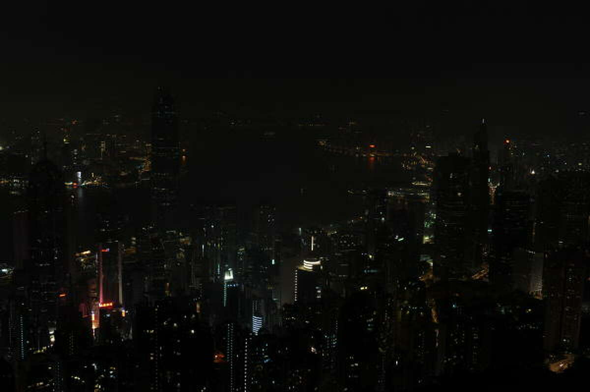 The skyline of Hong Kong Island and Kowloon is seen shortly after the lights were switched off for Earth Hour in Hong Kong on March 27, 2010.