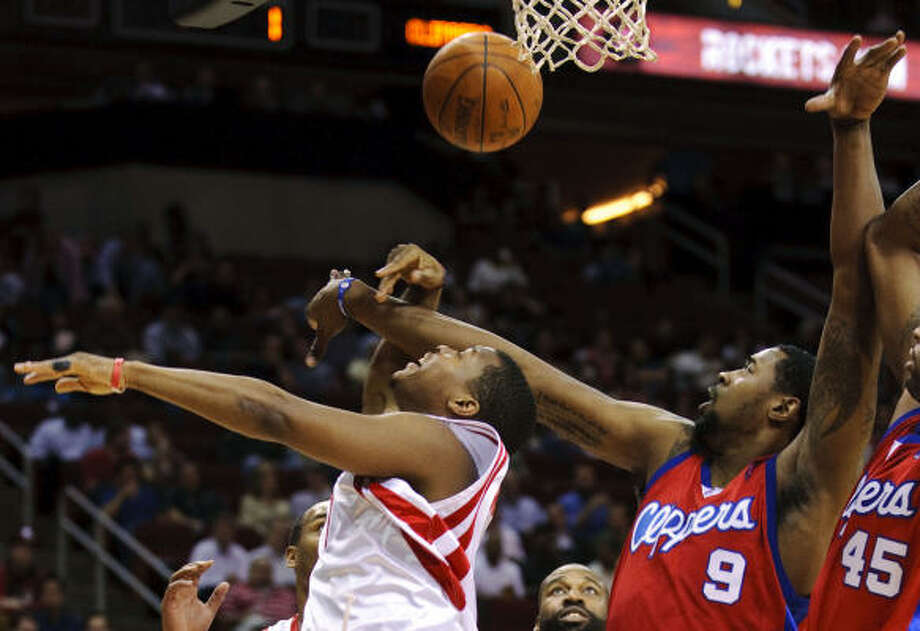 Rockets' Kyle Lowry, left, is fouled by Clippers' DeAndre Jordan (9) during the first quarter. Photo: Dave Einsel, AP