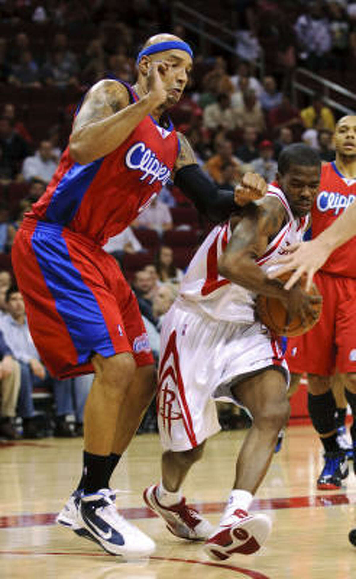 Rockets guard Aaron Brooks, right, drives around Clippers' Drew Gooden. Brooks finished with 18 points and dished out nine assists.