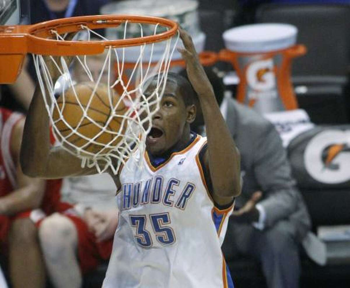Former University of Texas player and current Thunder forward Kevin Durant dunks against the Houston Rockets.