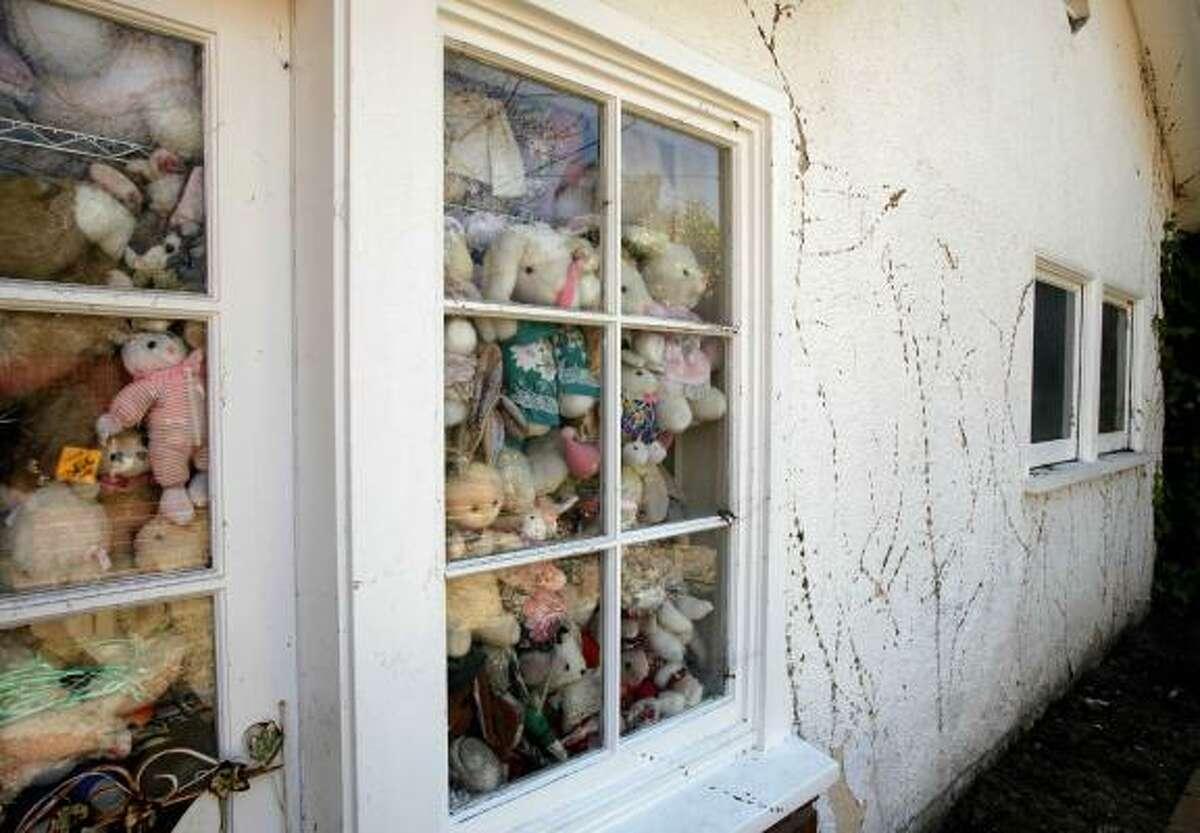 Stuffed bunnies fill a living room window.