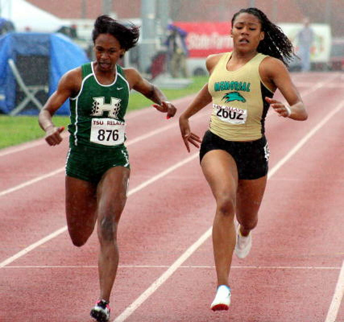 Hightowers' Kayla Savoie, left, and Pasadena Memorial's Isis Wilson fight the rain to the finish line.