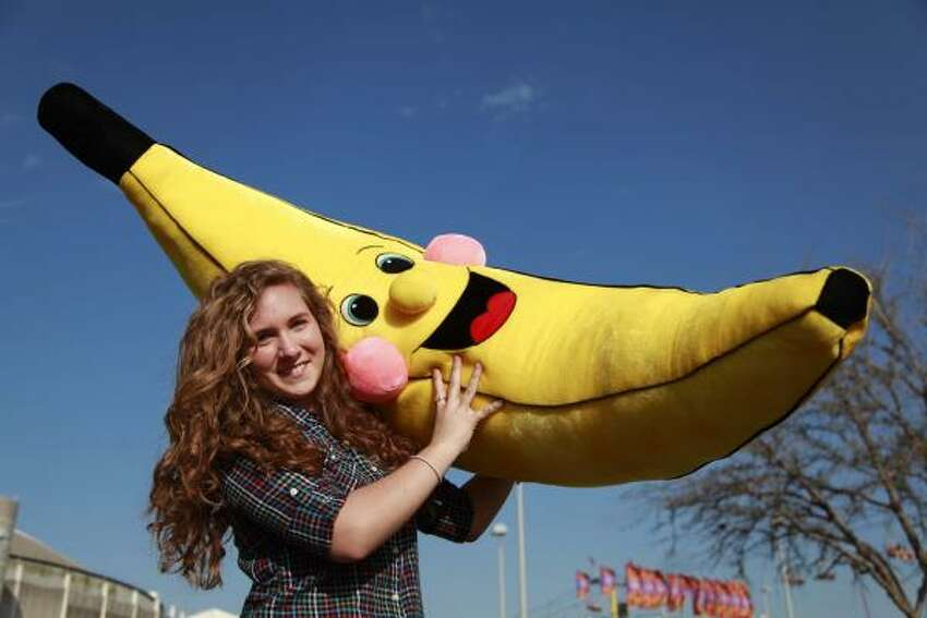 BIG BANANA: Kaleigh Hewlett, 19, carries the oversized prize she won playing a hoops game.