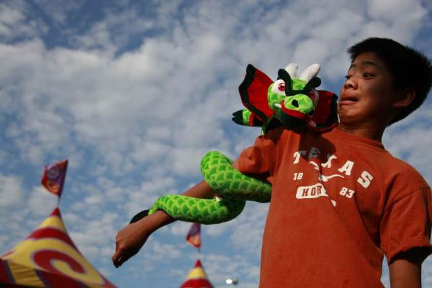 WELL-ARMED: Andy Nguyen, 14, is rewarded for his skill at a balloon-dart game.