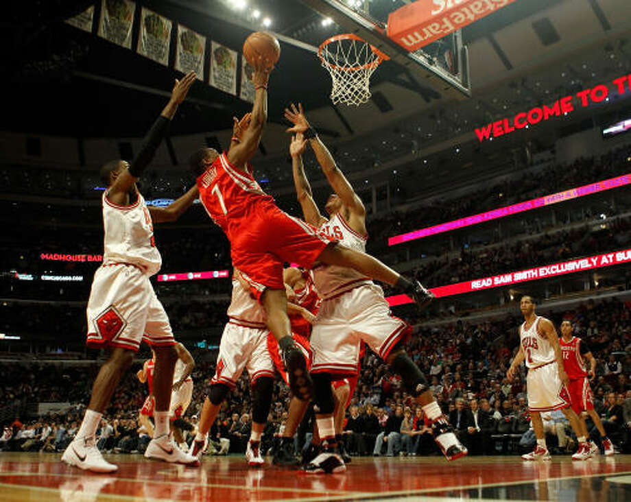 Rockets Kyle Lowry puts up a shot between Hakim Warrick and Derrick Rose of the Chicago Bulls. Lowry finished with 10 points. Photo: Jonathan Daniel, Getty Images