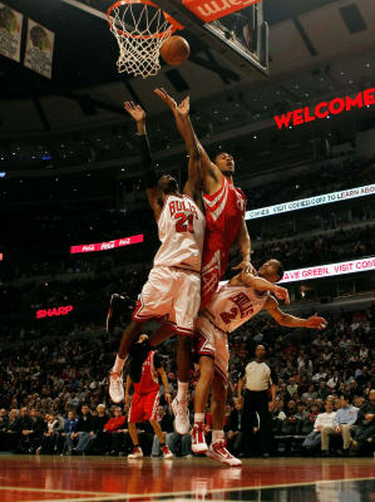 Jared Jeffries of the Houston Rockets tries to put up a shot between Hakim Warrick, left,and Jannero Pargo of the Chicago Bulls. Jeffries left the game with a strained left Achilles.
