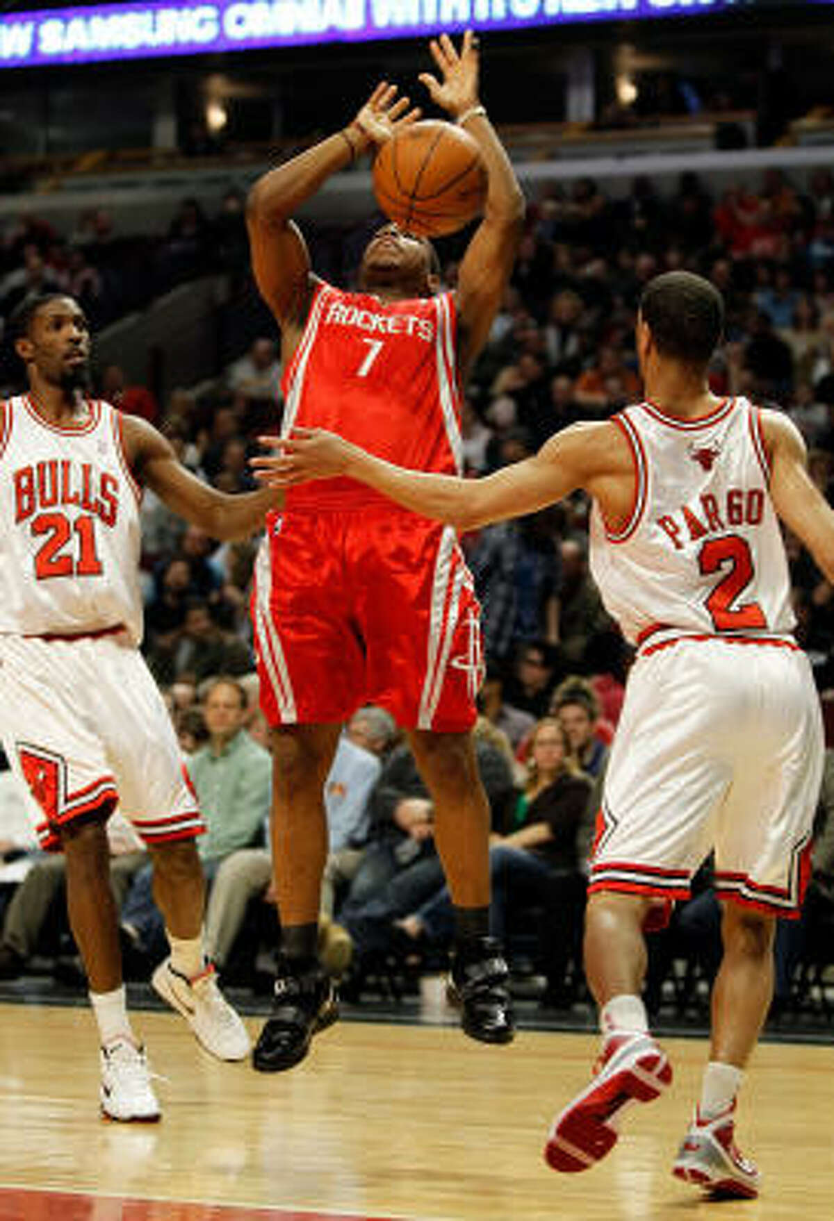 Rockets guard Kyle Lowry loses control of the ball between Hakim Warrick and Jannero Pargo of the Chicago Bulls.