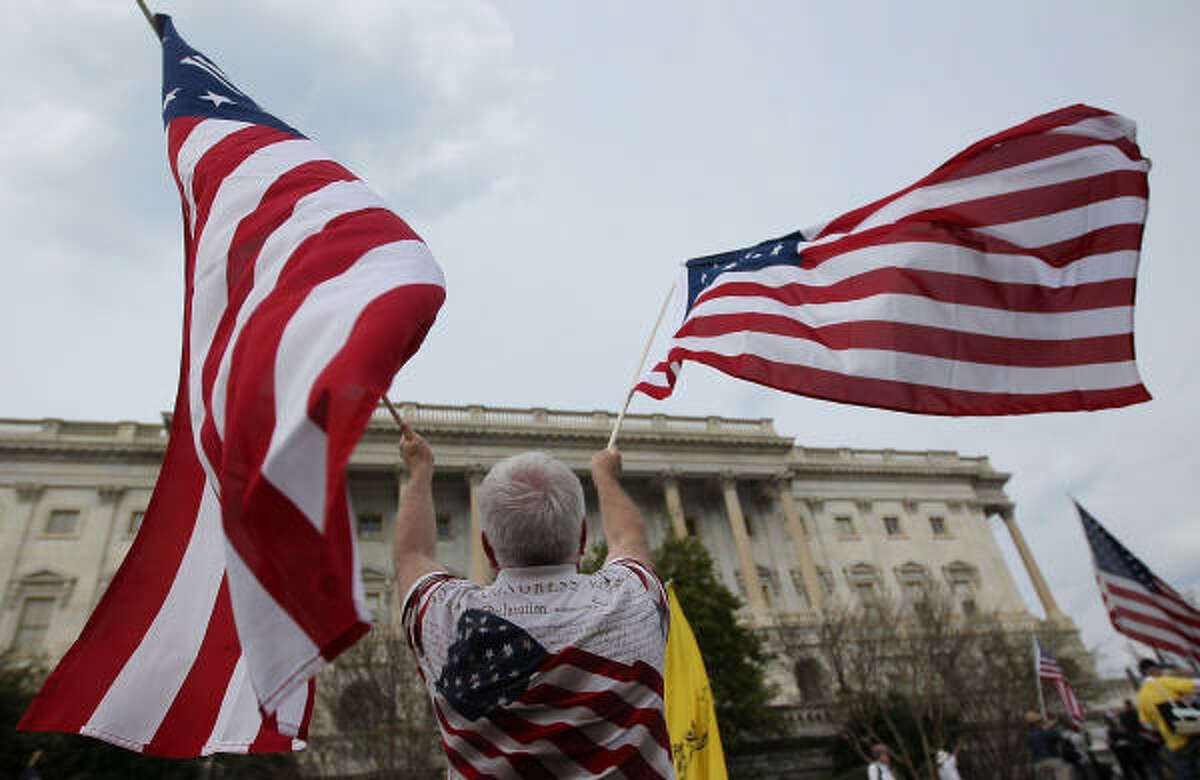 Demonstrator Don Creek, of Florida, waves two American flags.