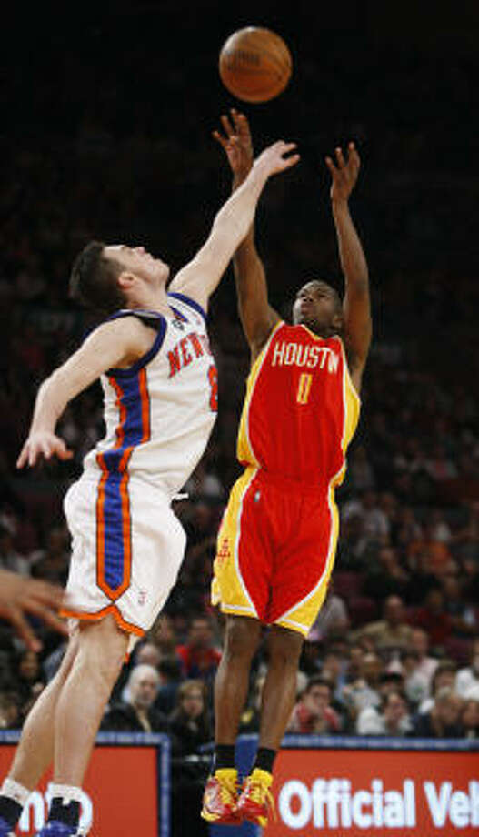 Rockets guard Aaron Brooks (0) shoots a three pointer over New York Knicks forward Danilo Gallinari, left, in the fourth quarter. Brooks scored 16 points in the Rockets 116-112 victory over the New York Knicks. Photo: Kathy Willens, AP