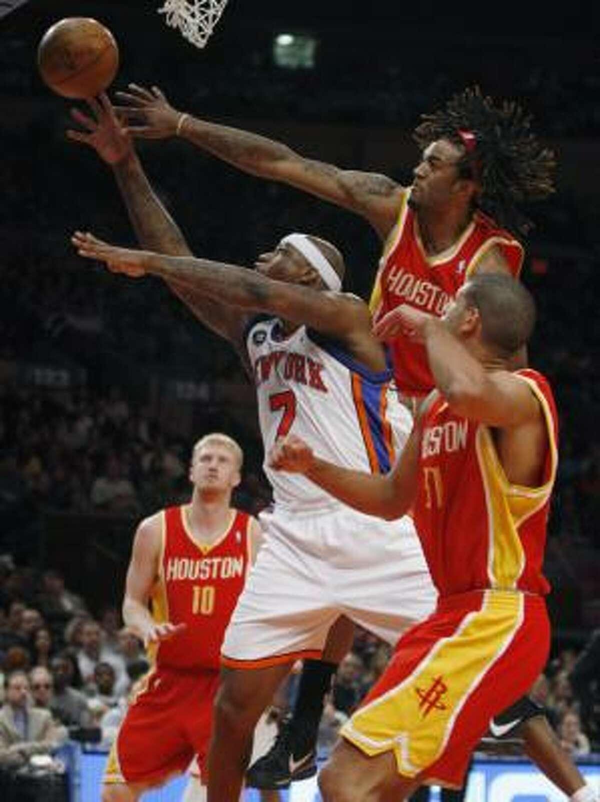 Rockets forward Jordan Hill (27) knocks the ball from New York Knicks forward Al Harrington (7) as Rockets Chase Budinger (10) and Rockets Shane Battier (31) defend.