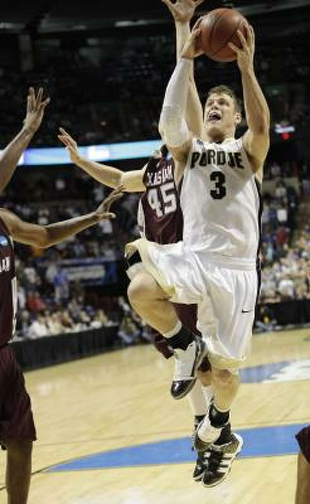 Purdue's Chris Kramer goes in for the game-winnnig basket past the defense of Texas A&M's Nathan Walkup (45) in overtime.