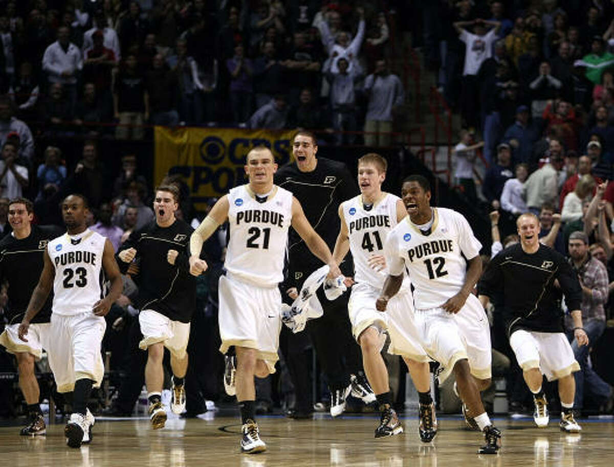Members of the Purdue Boilermakers rush the court in celebration after defeating the Texas A&M Aggies 63-61 in overtime.