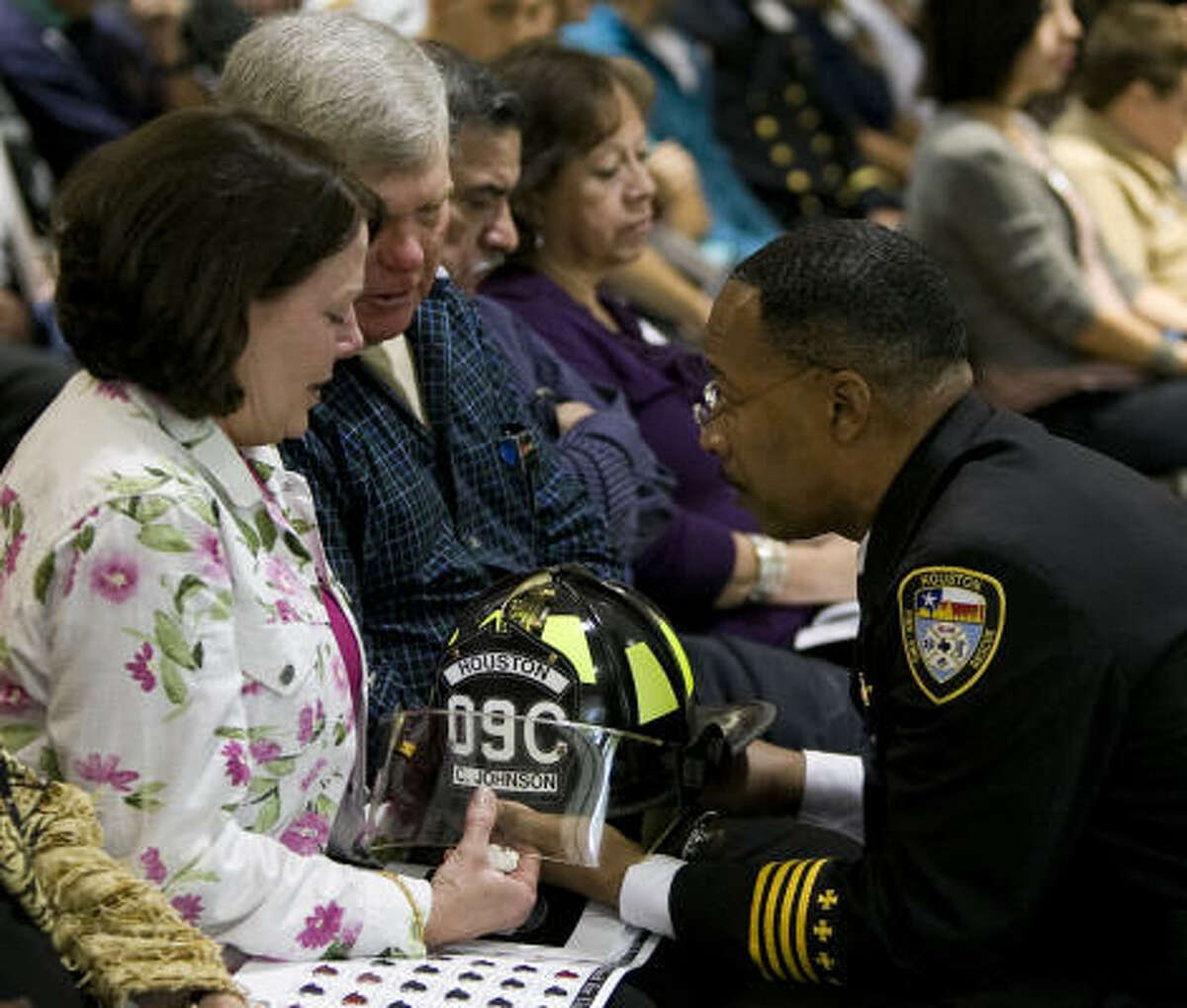 Candice Johnson, front, and her husband Clifford Mike Johnson, parents of fallen HFD cadet Cohnway Johnson, are presented with their son's firefighting helmet from HFD Chief Rick Flanagan during The Houston Fire Department Memorial Ceremony. Cohnway Johnson died in May of 2009 of hyperthermia and dehydration.