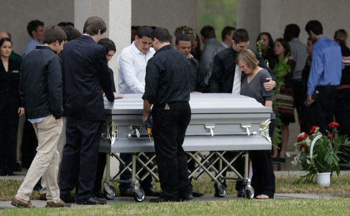 Mourners at the casket of Marine Lance Cpl. Garrett Gamble after service at Houston National Cemetery.