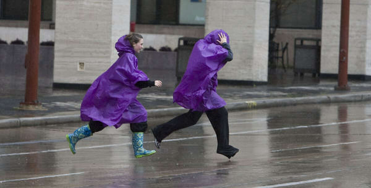 Two people run across Louisiana avenue at Jones Plaza in Houston.