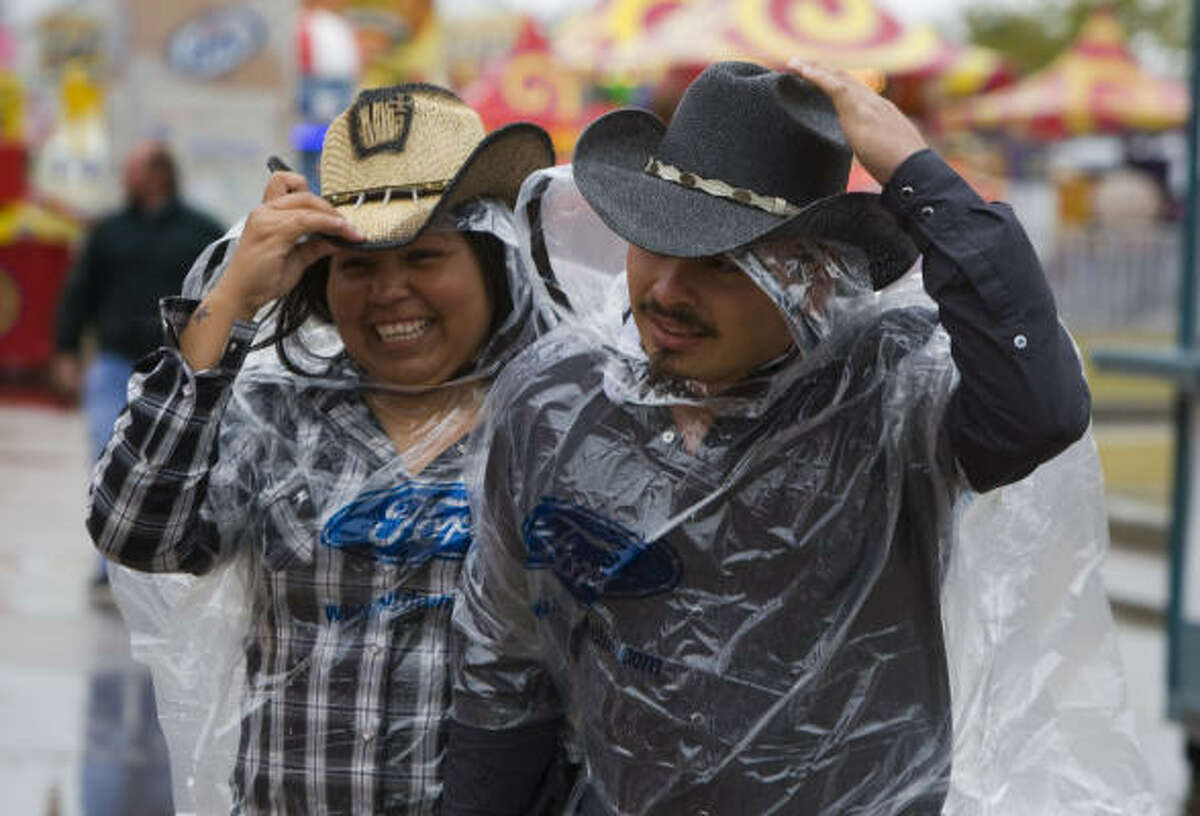 Jessica Vasquez, left, and Jesus Velasquez hold onto their hats as they walk in the wind and rain outside Reliant Stadium.