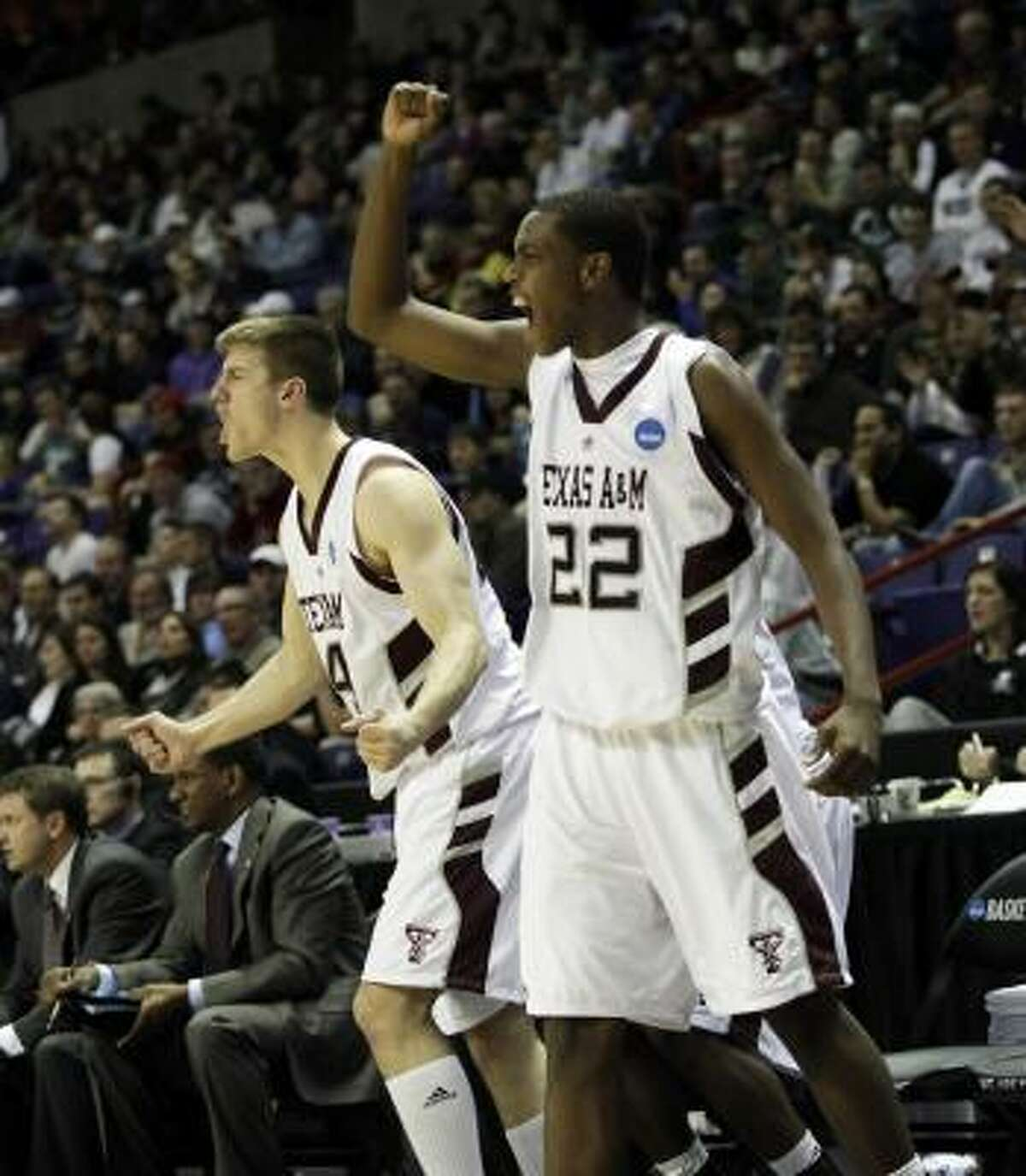 Texas A&M's Khris Middleton, right, and Nathan Walkup cheer from the bench late in the second half.