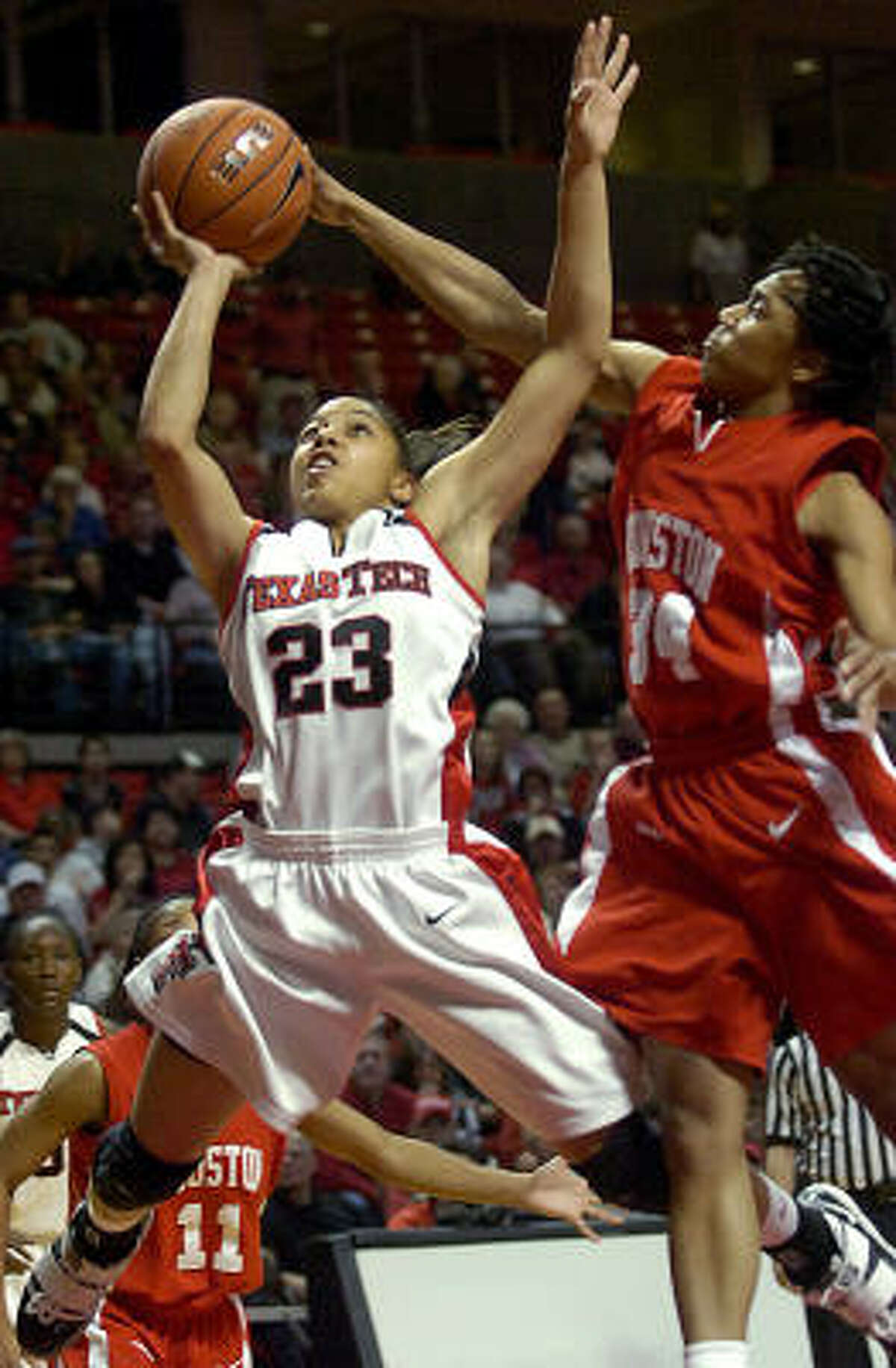 Texas Tech's Monique Smalls, left, is defended by Houston's Jasmine Johnson during the first half.