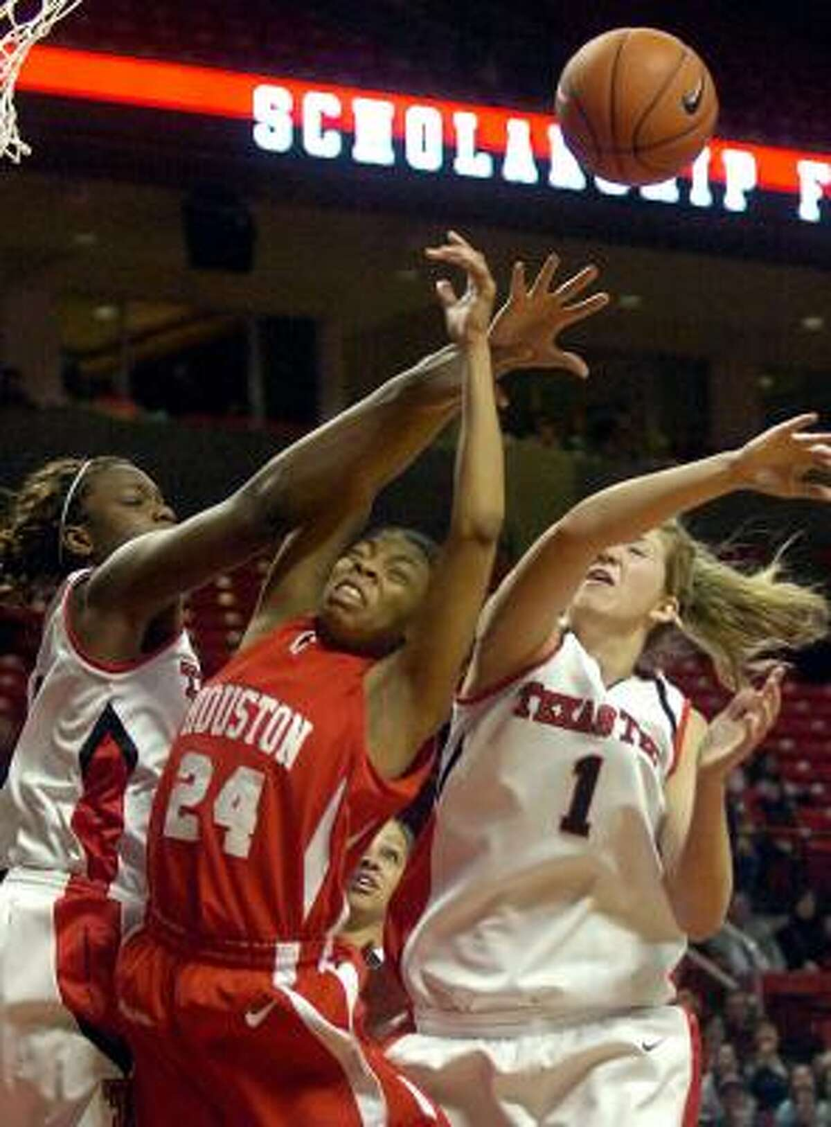 Texas Tech's Christine Hyde, left, and Jordan Barncastle, right, battle for a rebound with Houston's Courtney Taylor.