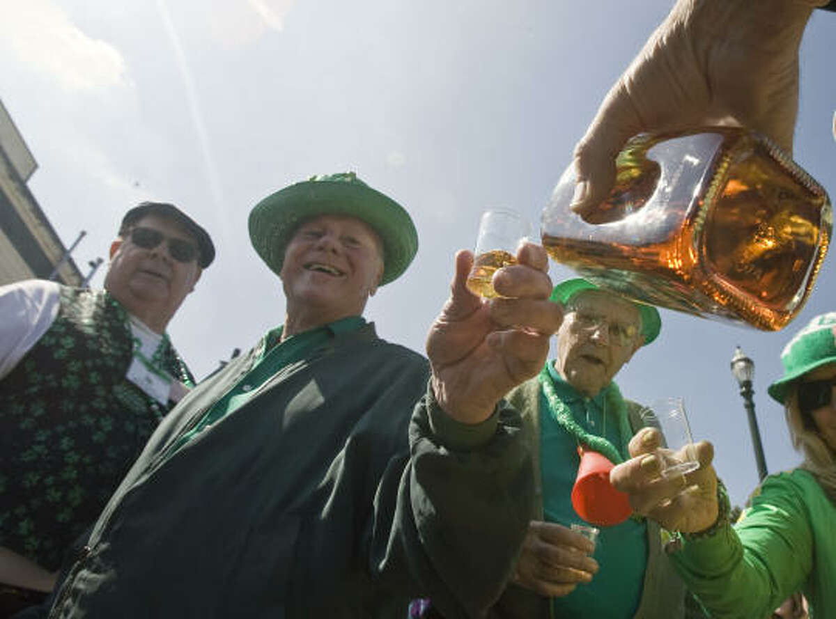 Charlie Dodson has a shot glass filled with whiskey as Michael Griffin and Jim Saye look on during the Slippery Rock Booster Club dying of the bayou event commemorating St. Patrick's Day along the banks of Buffalo Bayou.