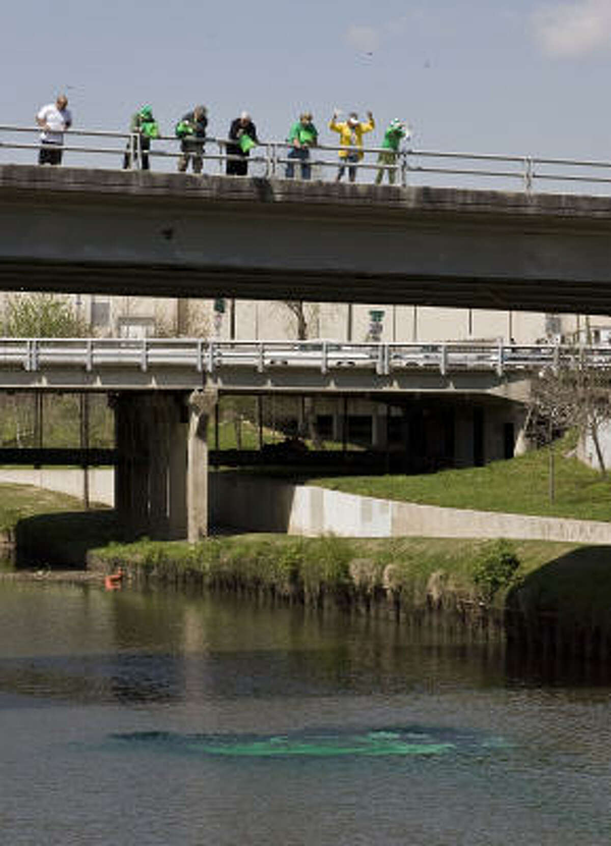 Members of the Slippery Rock Booster Club pour dye off a bridge during the dying of the bayou event commemorating St. Patrick's Day.