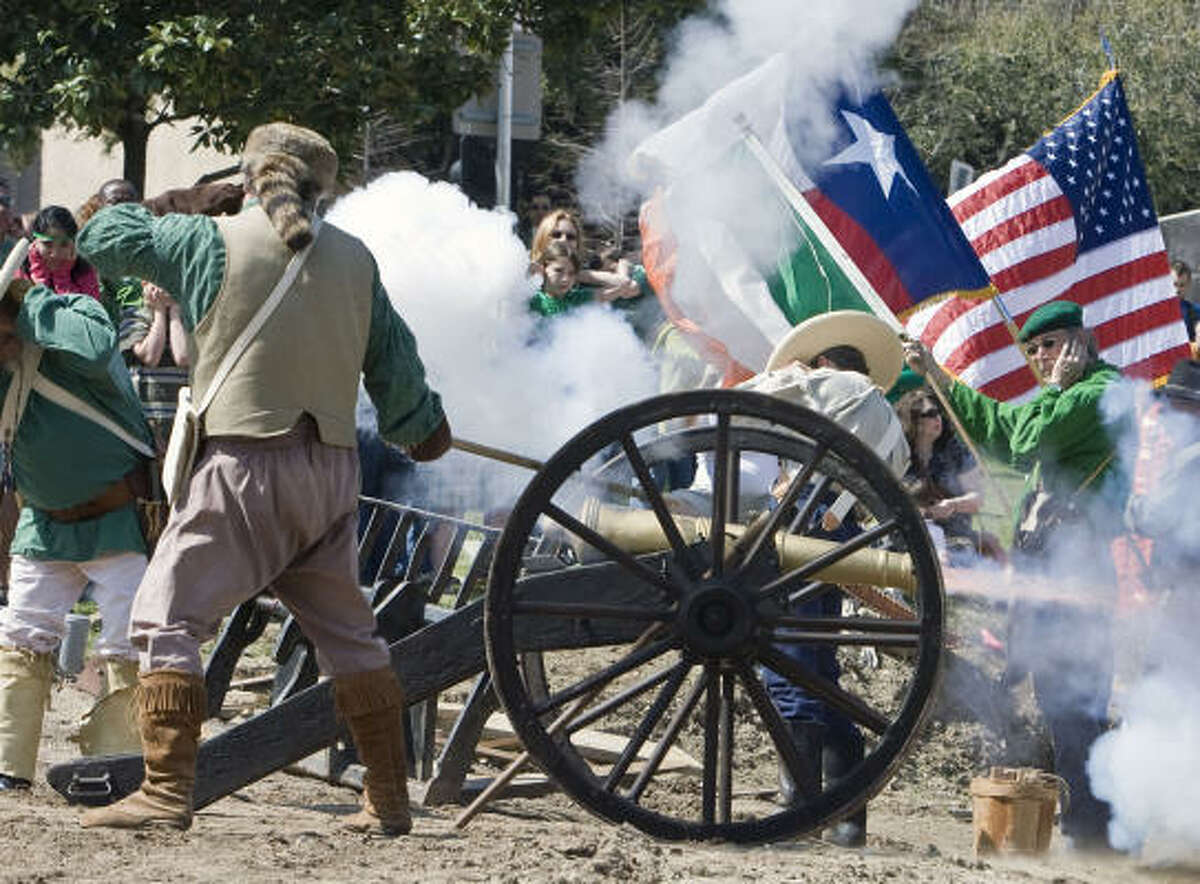 The Texas Army's Larry Joe Miggins covers his ears as Col. Sam Martin fires a canon loaded with dye during the Slippery Rock Booster Club dying of the bayou event commemorating St. Patrick's Day along the banks of Buffalo Bayou.