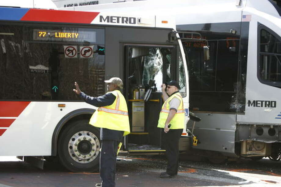 Damage to a Metro bus is seen after it collided with a MetroRail train Monday at the corner of St. Joseph and Main downtown. Photo: Julio Cortez, Chronicle