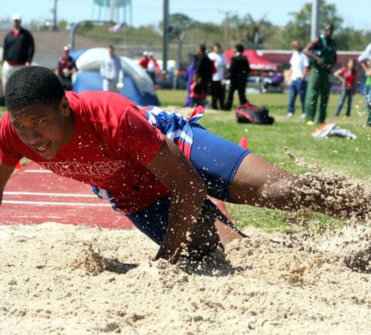 Dulles' Diamaal Holmes lands with force in the triple jump.