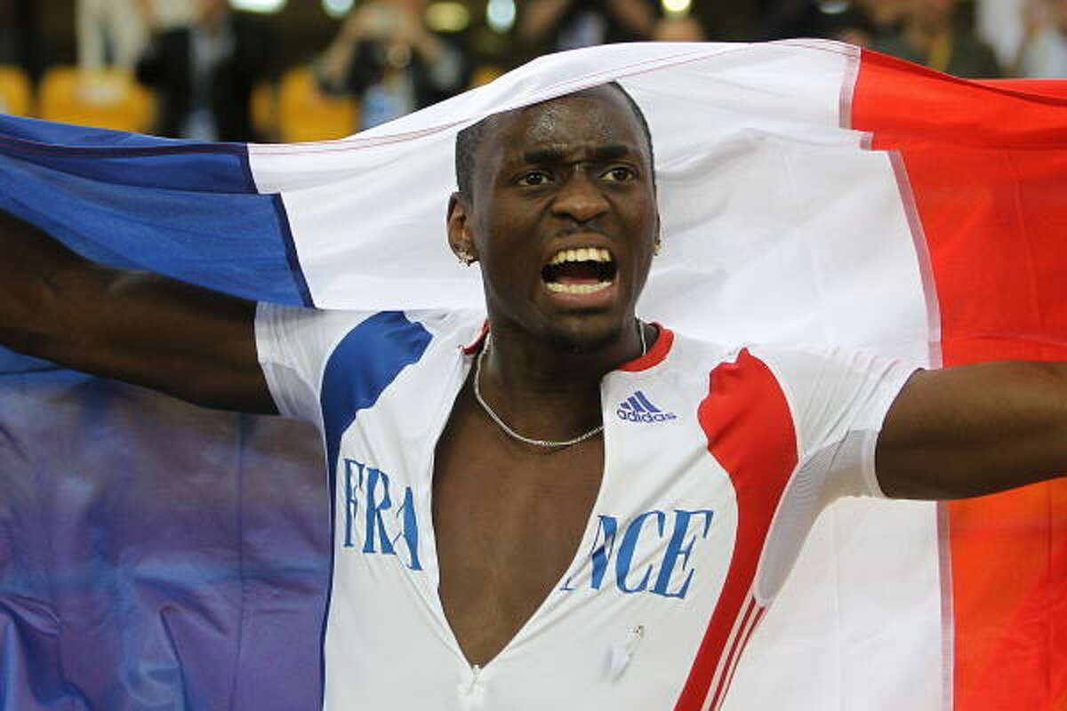 Teddy Tamgho celebrates with France's national flag after his record-setting performance.