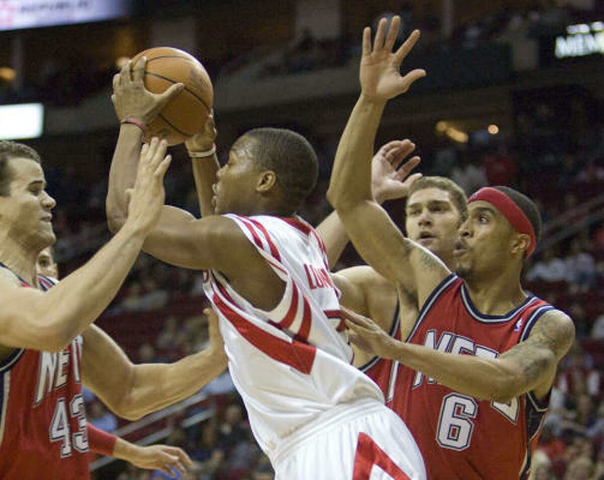 Rockets guard Kyle Lowry tries to maneuver through Nets defenders Kris Humphries (43), Brook Lopez, second from right, and Courtney Lee (6).
